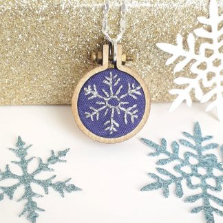Hand embroidered glitter thread snowflake on purple cotton fabric. Set in a wooden mini embroidery hoop measuring 2.5cm