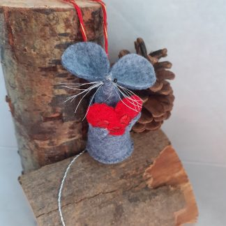 a handmade felt mouse hugging a red felt heart decorated with sequins