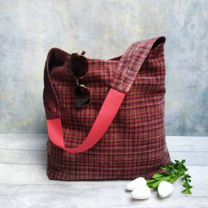 Red tones woven upholstery fabric large hobo style shoulder bag pictured with tulips, foliage and sunglasses