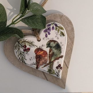 A 2 layer wooden hanging heart decoupaged with a unique design; 2 birds sitting on a branch amongst leaves, berries and wildflowers. Finished with a natural twine hanger