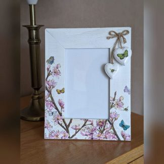 A whitewashed 6 x 4 inch photo frame decoupaged with a cherry blossom design and finished with 2 wooden hanging hearts