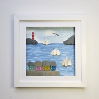 framed coastal wall decor featuring brightly coloured houses and lighthouse