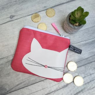 Pink purse or make up bag with white stylised cat motif . Pictured with chocolate coins and cactus