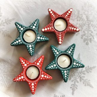 Christmas star tea light holders with nordic snowflake design in red and teal on a table