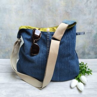upcycled denim hobo cross body bag with a chartreuse taffeta lining and khaki strap pictured with sunglasses and flowers