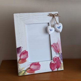 Whitewashed photo frame with a decoupaged tulip design and 2 wooden hearts hanging from a twine bow.
