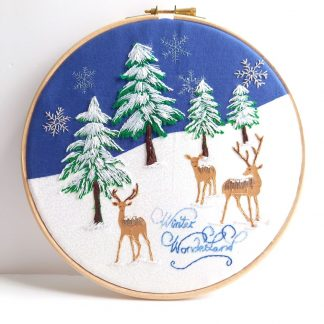 Snowy winter wonderland scene, hand embroidered 8 inch hoop featuring a family of deer's amongst snow filled fir trees.