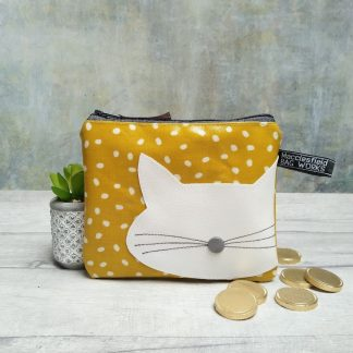 mustard yellow spotted oilcloth purse or makeup bag with a retro cat motif. Pictured with chocolate coins and a cactus plant