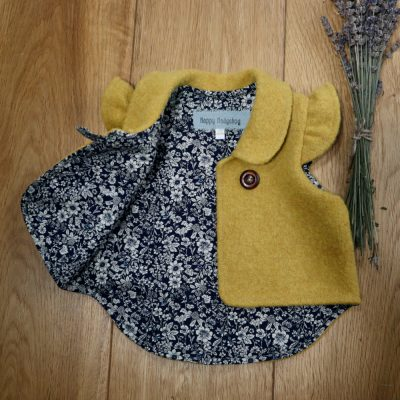 A mustard yellow baby gilet opened to show a navy ditsy floral lining, a collar & flutter sleeves
