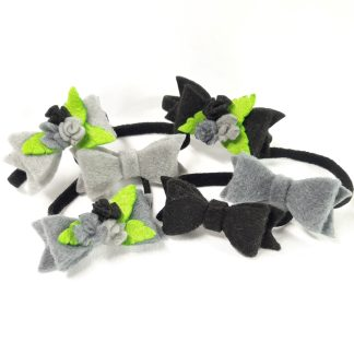 Hair elastic bands with black and grey felt bows and roses in the same shades with green leaves.