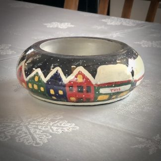 Christmas bowl with village design on a table showing the toy shop