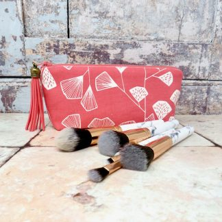 A zipped pouch in coral pink and with a faux suede tassel