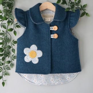 A teal blue baby sized jacket with collar, flutter sleeves and a large flower motif