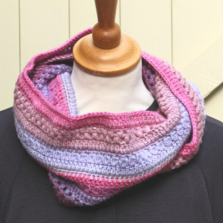 a crochet infinity scarf in stripes of pink, lilac, lavender and white. It is displayed on a tailores dummy and there is a cream fence in the background
